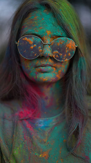 Portrait of woman standing being covered in coloured powder at holi festival.