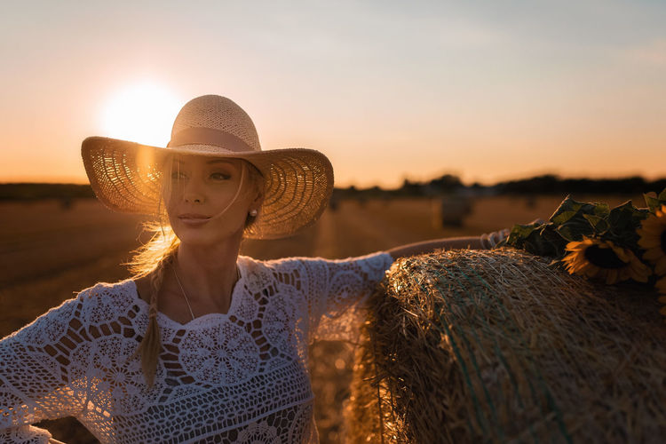 Portrait of woman with hat on beach against sky during sunset