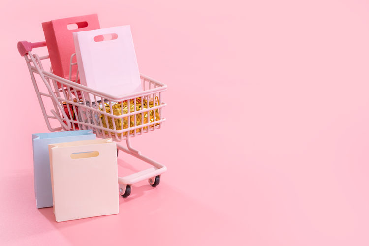 Close-up of shopping bags in cart against pink background