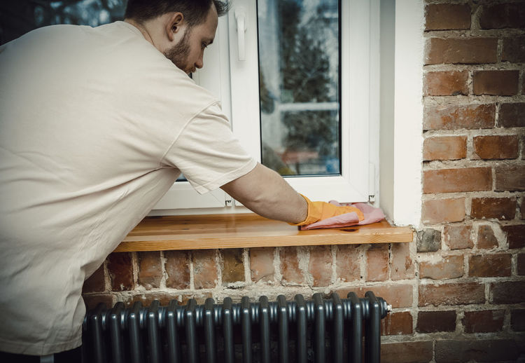 Man Cleaning Window Sill