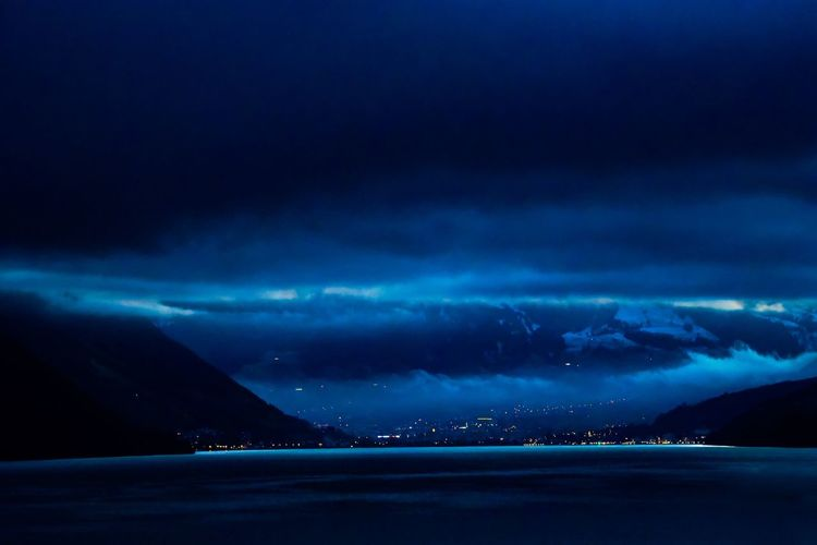 Scenic view of sea against storm clouds at night
