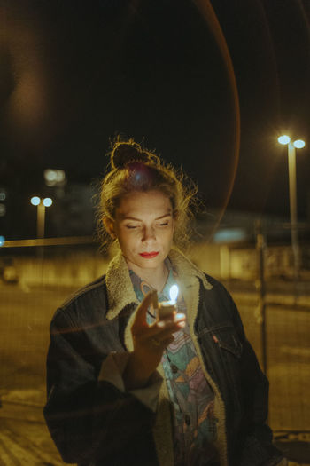 Portrait of young woman holding illuminated lighting equipment at night