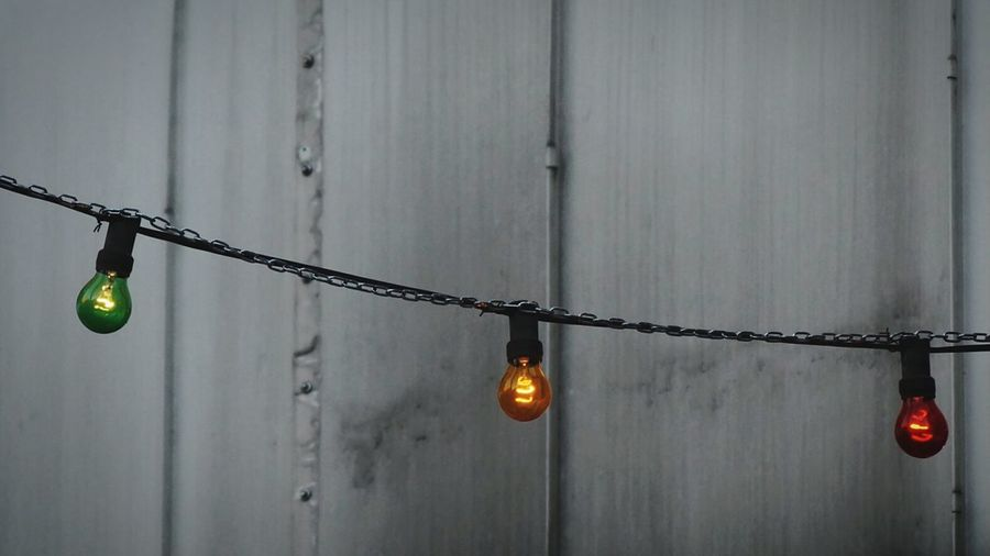 Low Angle View Of Lighting Decoration Hanging Against Wooden Wall