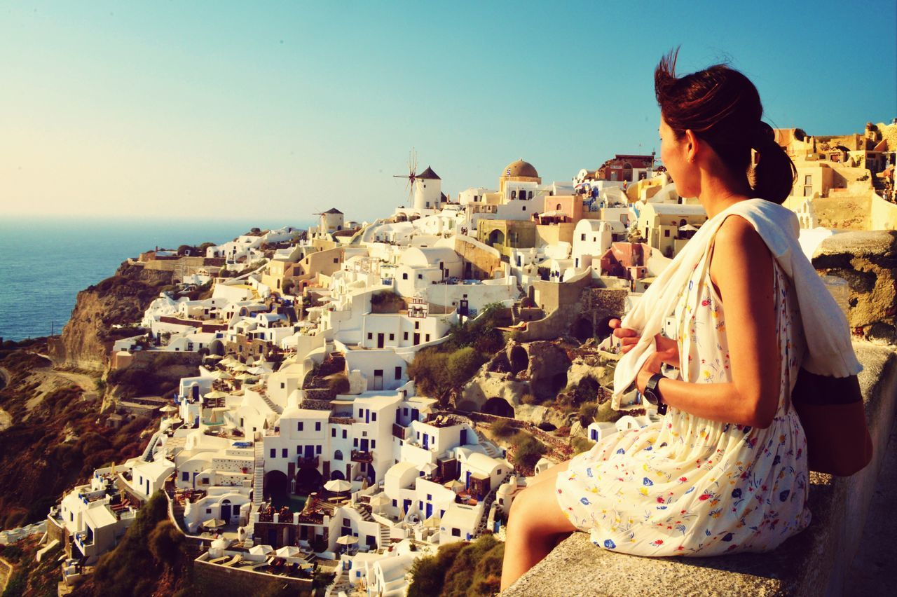 Greece, Woman Looking At Townscape At Seaside