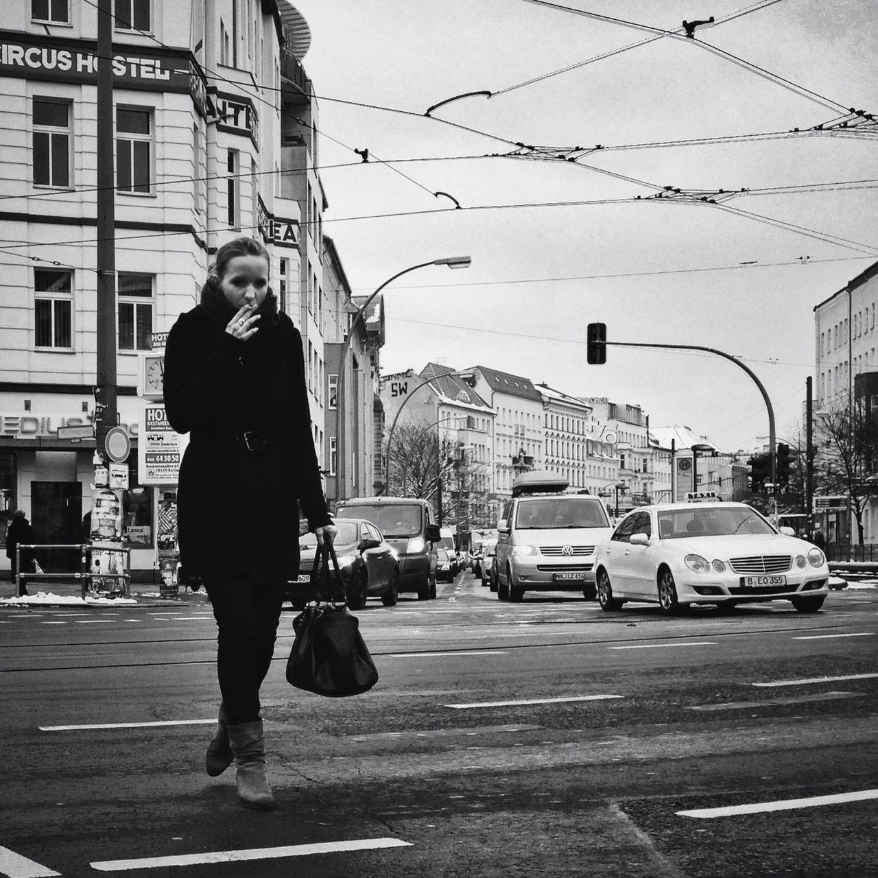 WOMAN WALKING ON CITY STREET AGAINST SKY