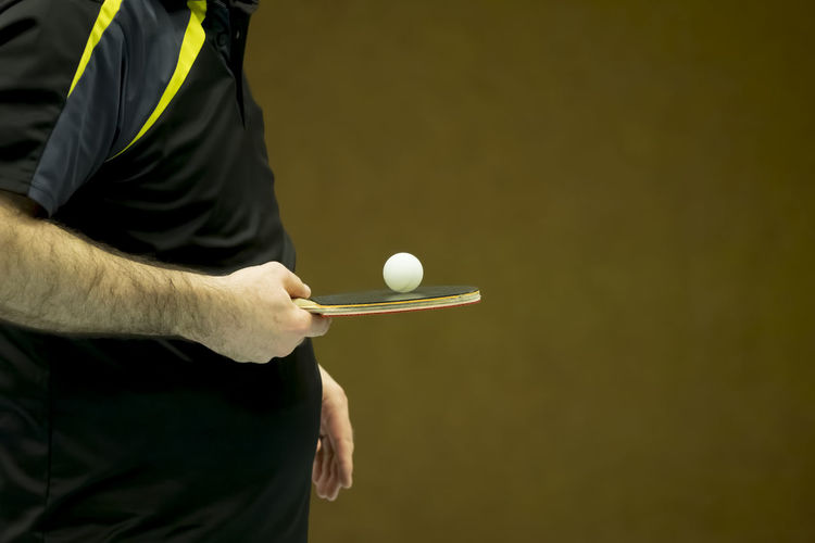 Midsection of man playing table tennis against brown wall