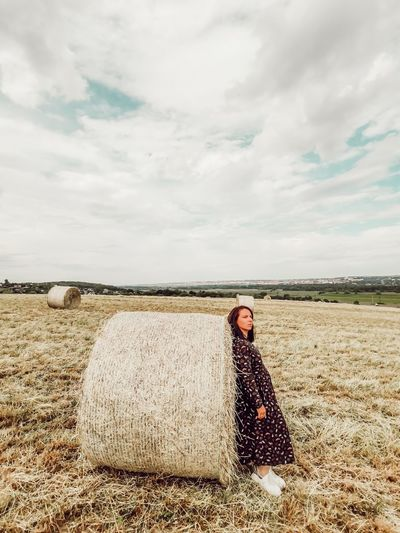 Woman standing by hay bales on field against sky