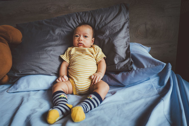 High angle view of baby lying on bed at home
