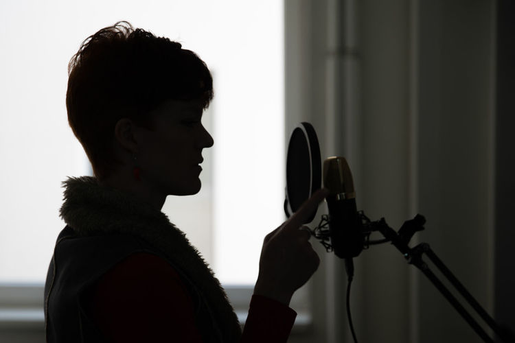Side view of woman singing in studio