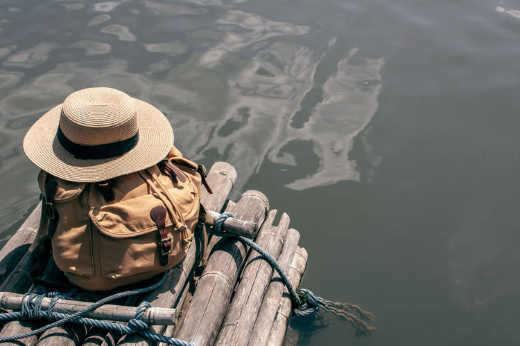 High Angle View Of Bag And Hat On Wooden Post By Lake