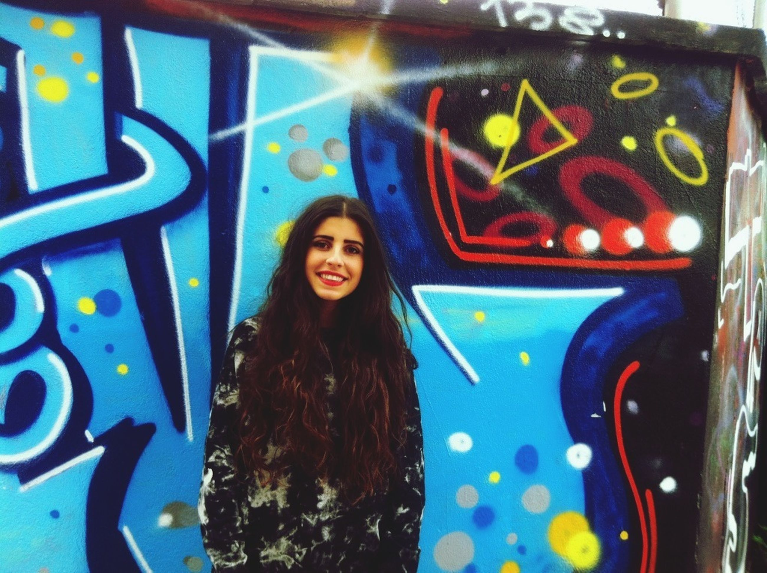 graffiti, art, creativity, looking at camera, portrait, art and craft, multi colored, front view, young adult, indoors, wall - building feature, long hair, lifestyles, person, human representation, leisure activity, casual clothing, young women