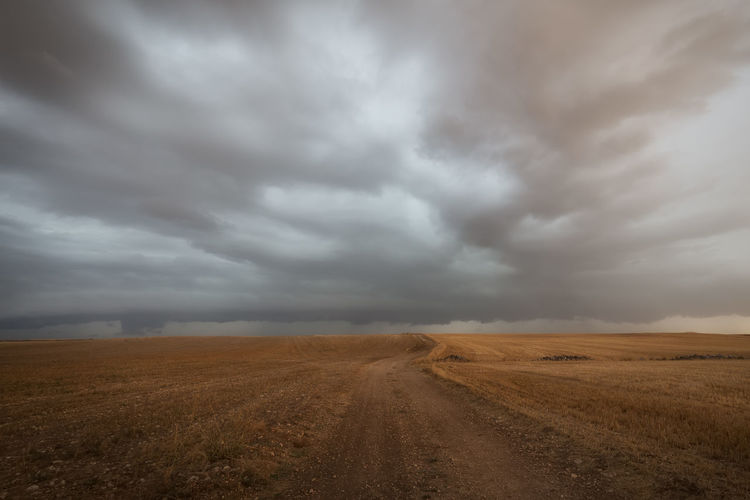 Dirt road passing through land against cloudy sky