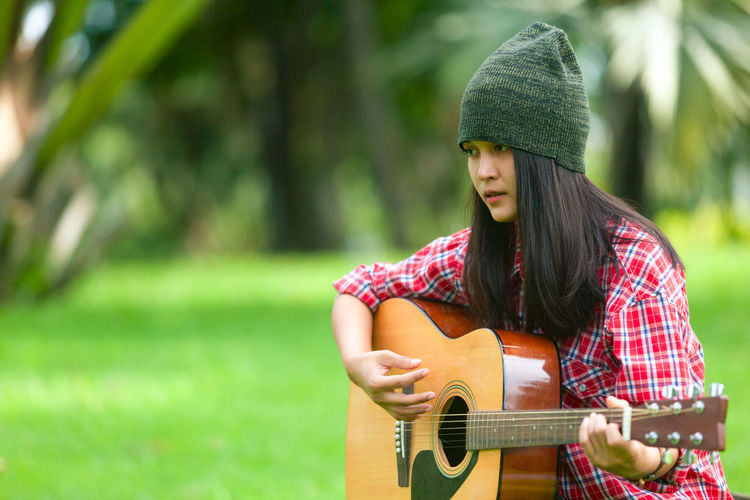 Thoughtful young woman playing acoustic guitar at park