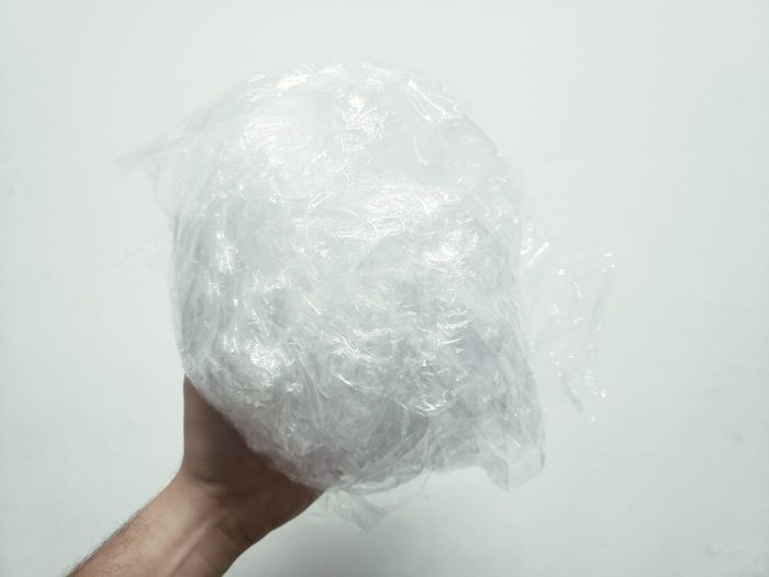 Close-up of hand holding ice over white background