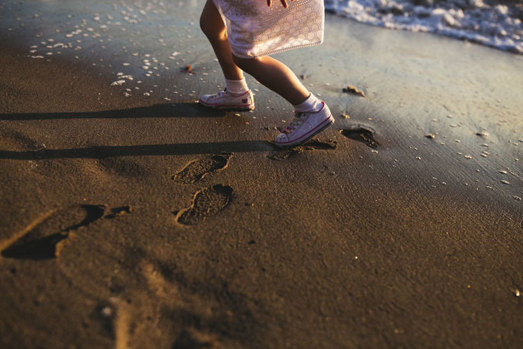 Barefoot Beach Casual Clothing Child Playing Childhood Day Footprints In The Sand Fun Girl Leisure Activity Little Girl Low Section Outdoors Person Play Playing Sand Selective Focus Shadow Tourism Vacations Walking Weekend Activities