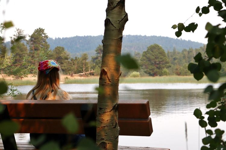 Woman looking at lake against trees