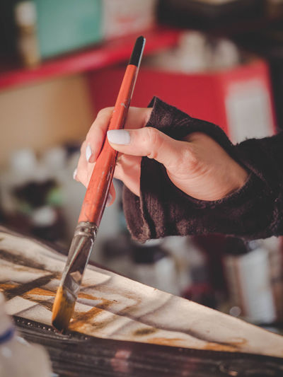 Close-up of female painter hand holding paintbrush while painting on canvas