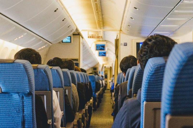 Air travel. Travel Air Travel  Transportation Vehicle Seat Vehicle Interior Mode Of Transportation Travel Passenger Group Of People Lifestyles Airplane Seat Air Vehicle Real People Airplane Passenger Cabin Public Transportation Seat Sitting Journey Men Women Commercial Airplane