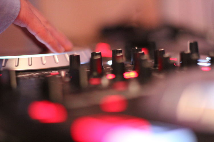 Cropped Hand Of Dj Playing Turntable In Nightclub