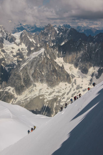 High angle view of people climbing snowcapped mountain