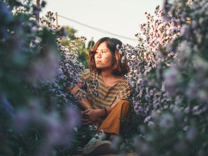 Woman standing on purple flowering plants