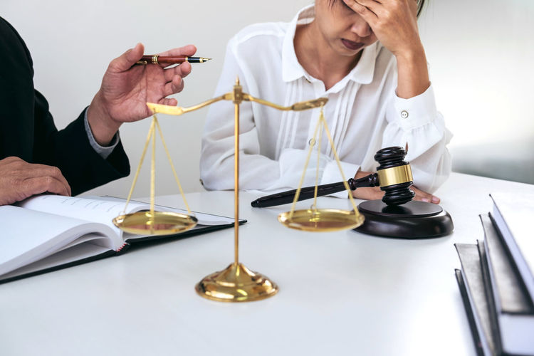Midsection of judge with female client sitting at desk