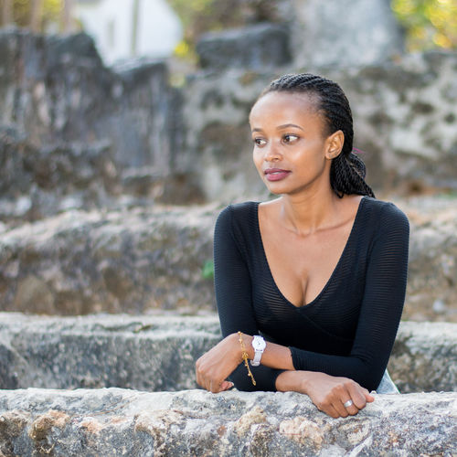 Thoughtful young woman standing by retaining wall