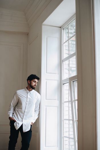 a young man of oriental appearance sits by the window One Person Standing Indoors  Three Quarter Length Window Young Adult Young Men Casual Clothing Home Interior Hands In Pockets Men Day Real People Adult Button Down Shirt Lifestyles Front View Architecture Contemplation Hairstyle