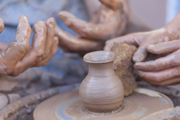 Pottery in making Teaching Art And Craft Clay Craft Creative Creativity Expertise Finger Focus On Foreground Hand Human Body Part Human Hand Making Molding A Shape Mud Occupation People Pottery Preparation  Real People Skill  Spinning Working