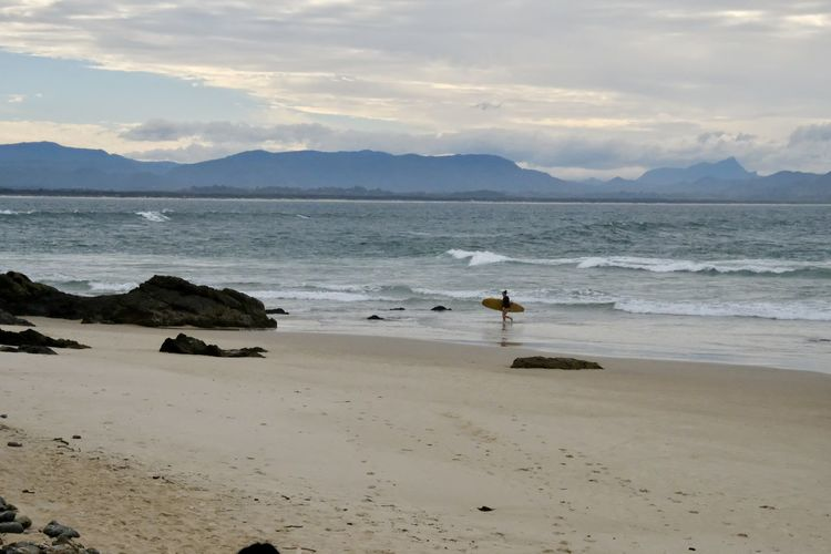 Lone surfer Beach Beauty In Nature Day Mountain Nature No People Outdoors Sand Scenics Sea Shore Sky Sunset Tranquility Water Wave