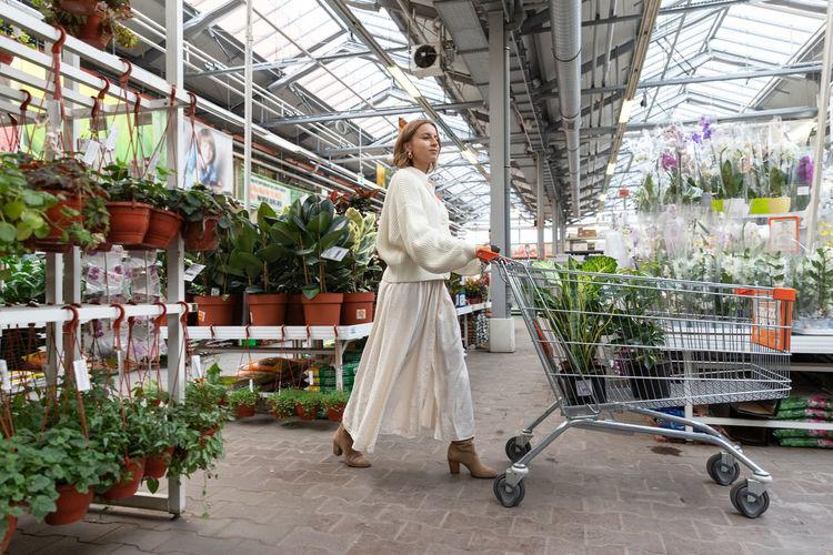 Full length of woman walking in greenhouse