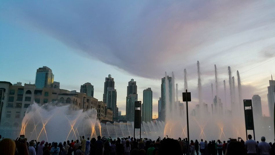 The fountain Water Fountains Dubai Mall Urban Skyline Cityscape Clouds And Sky Tourist Attraction  Tourists Evening Sky Evening Light Beauty In Nature Evening Shot Outdoors Dubai Dubai UAE Dubai Tourism Large Group Of People Real People Crowd Architecture Leisure Activity Lifestyles Travel Destinations Modern City