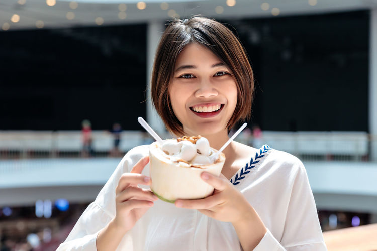 Portrait of a smiling young woman holding ice cream in restaurant