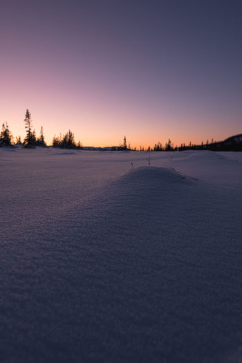 Scenic view of winter landscape against clear sky during sunset