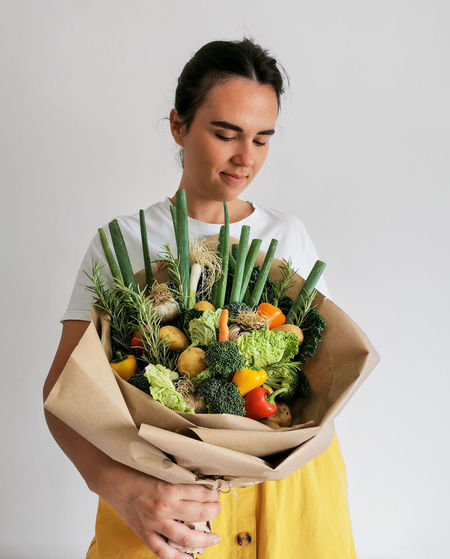 Young woman holding food against white background