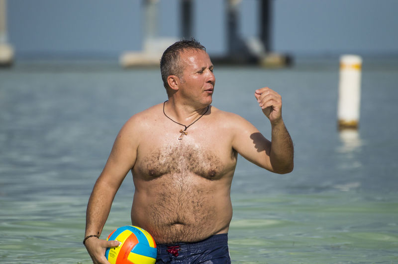 Full length of shirtless man standing in sea