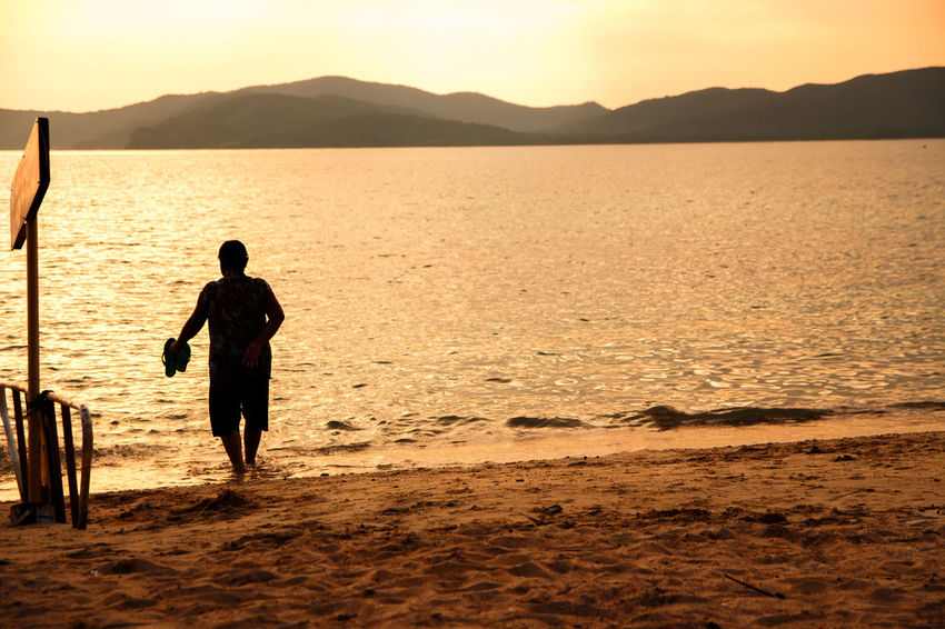 silhouette of people at the beach,The beauty of natural light at sunset. Water Sea Real People Beach Sunset Sky Mountain Land Beauty In Nature Rear View Leisure Activity Lifestyles One Person Scenics - Nature Nature Silhouette Men Full Length Outdoors Silhouette Happiness Happy People Holiday Relaxing Children Women Man Romantic Orange Clouds And Sky Love Family Summer Sunrise Boy Freshair Freedom Fun