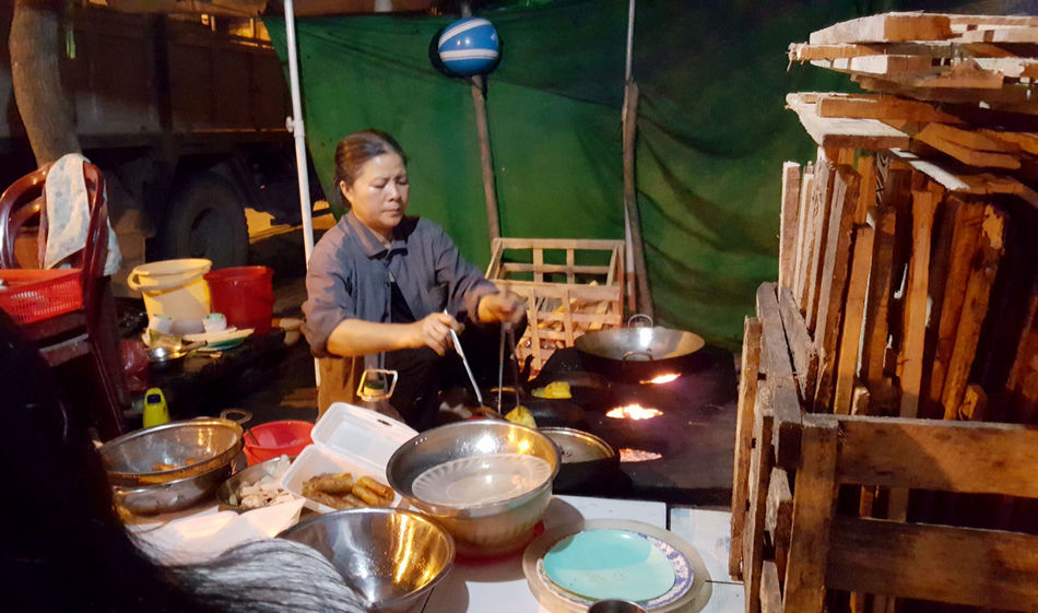 Woman cooking food on street stall in suburbs of Da Nang, Vietnam. Bowl Buckets Container Cooking Danang Dining Fires Flames Food Food Preparation Food Stalls Helmets Night Occupation Plastic Furniture Preparing Food Street Food Tradition Vietnam Vietnamese Cuisine Woks Wood