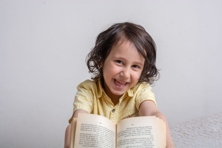 Portrait of a smiling girl holding book against white background