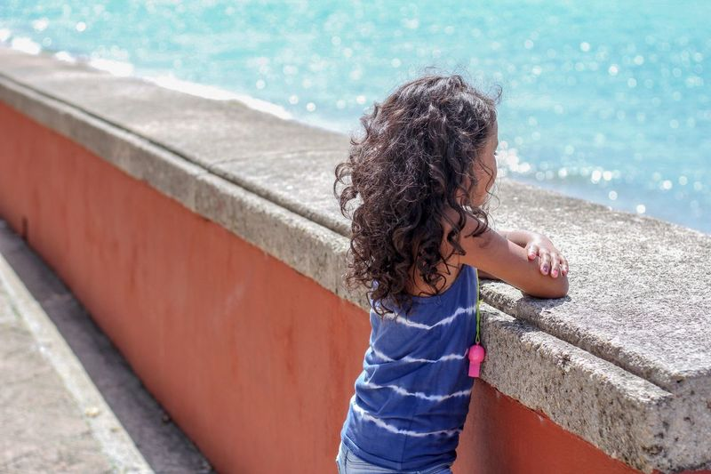 Side view of girl looking at sea while standing by retaining wall