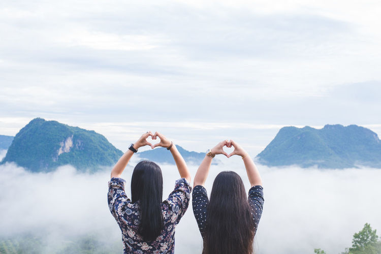Rear view of women making heart shape while looking at mountains