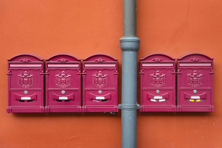 Close-up of pipe and mailboxes on orange wall