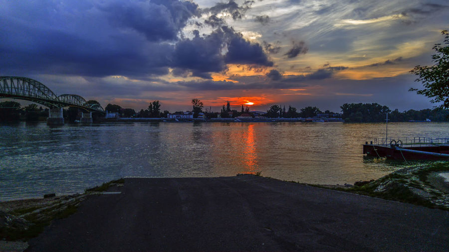 sunset Water Sky Cloud - Sky Sunset Architecture Built Structure Nature Beauty In Nature Orange Color Reflection Transportation Scenics - Nature No People River City Building Exterior Tranquility Nautical Vessel Outdoors