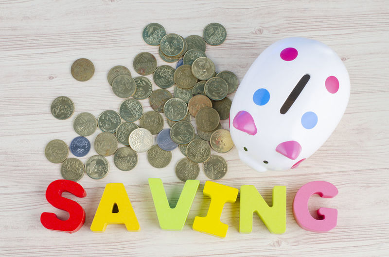 financial and saving money concept, piggy bank with stacking coins on wooden desk Multi Colored Indoors  Text Still Life High Angle View Western Script Table Wood - Material No People Capital Letter Alphabet Letter Communication Large Group Of Objects Red Number Close-up Directly Above Art And Craft Emotion