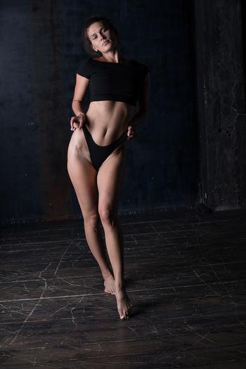 Portrait of woman wearing bikini standing on floor