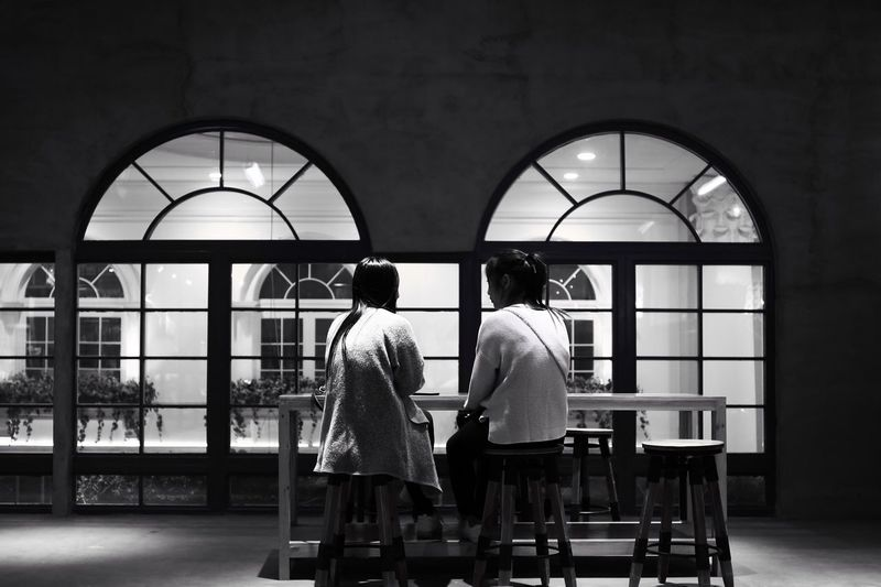 Rear View Of Friends Sitting In Restaurant At Night