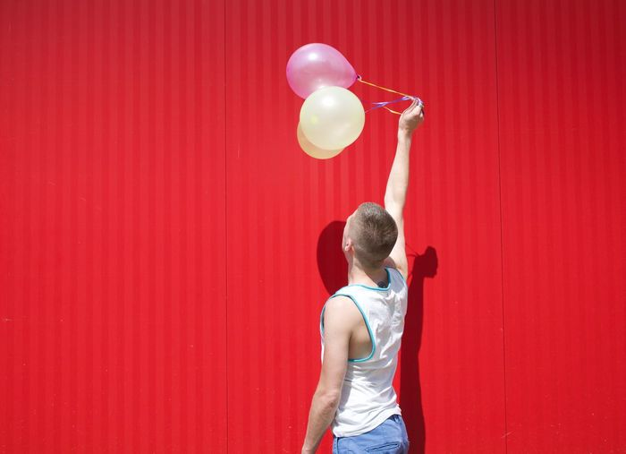 Man holding balloons while standing against red wall