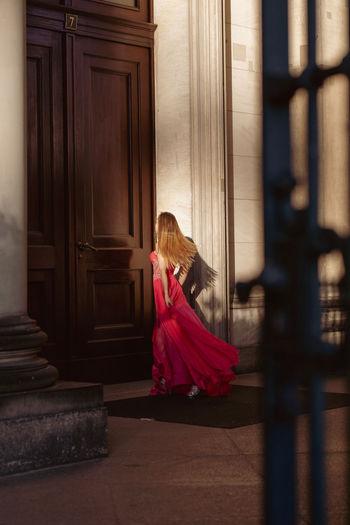 Full Length Of Woman Wearing Red Evening Gown Walking Towards Door