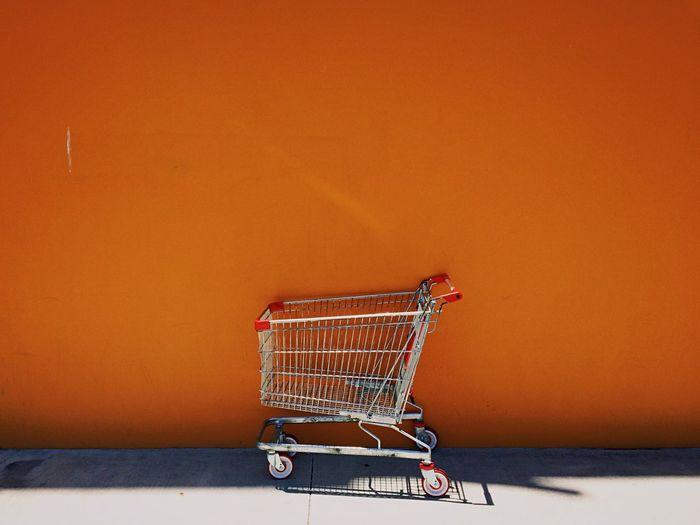 Shopping Cart Against Orange Wall