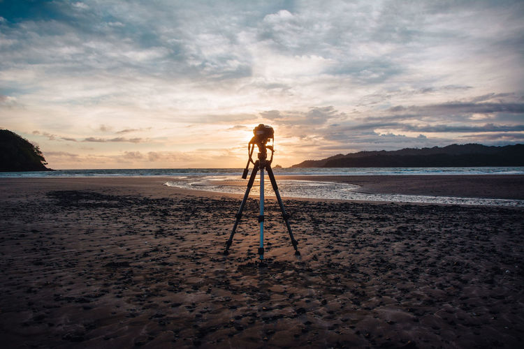 Tripod at beach against sky during sunset